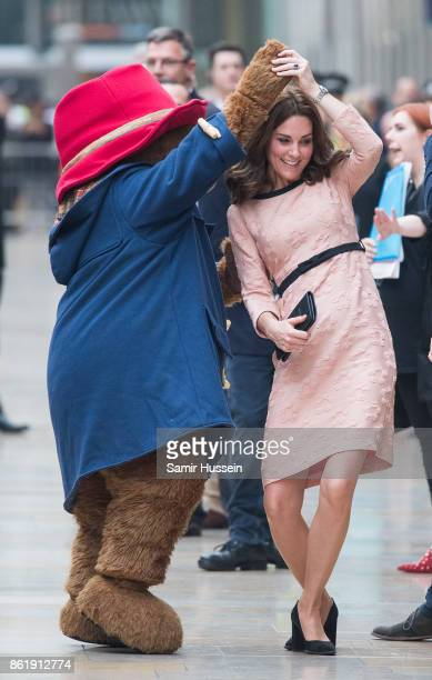 Catherine Duchess of Cambridge dances with Paddington Bear as she attends the Charities Forum Event on board the Belmond Britigh Pullman train at...