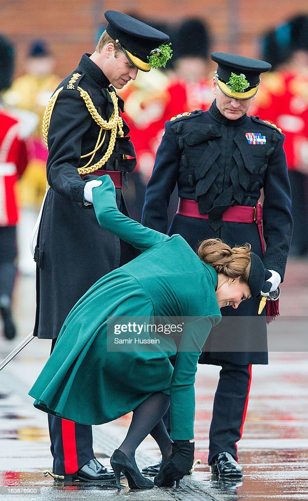 Catherine, Duchess of Cambridge gets her shoe stuck in the grating and is helped by <a gi-track='captionPersonalityLinkClicked' href=/galleries/search?phrase=Prince+William&family=editorial&specificpeople=178205 ng-click='$event.stopPropagation()'>Prince William</a>, Duke of Cambridge as they visit the Irish Guards' St Patrick's Day Parade at Mons Barracks on March 17, 2013 in Aldershot, England.