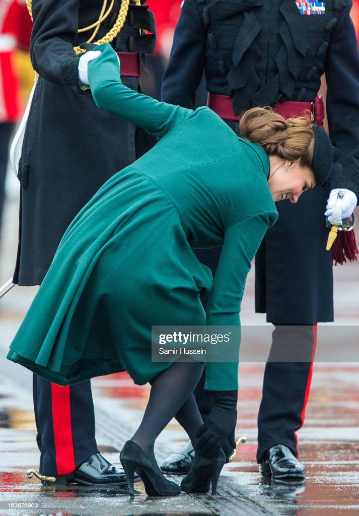 Catherine, Duchess of Cambridge gets her shoe stuck in the grating and is helped by Prince William, Duke of Cambridge as they visit the Irish Guards' St Patrick's Day Parade at Mons Barracks on March 17, 2013 in Aldershot, England.