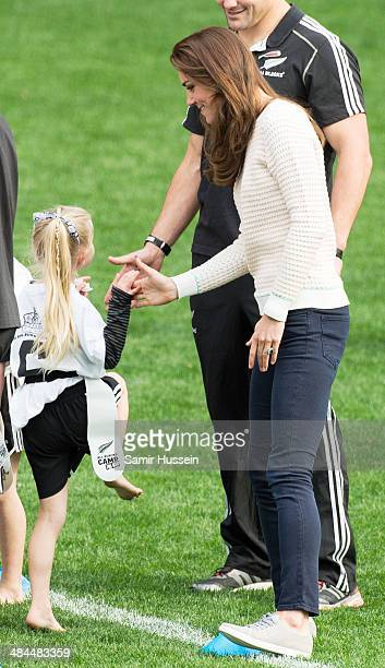 Catherine Duchess of Cambridge high fives a girl as she attends a young players' Rugby tournament at Forsyth Barr Stadium on April 13 2014 in Dunedin...
