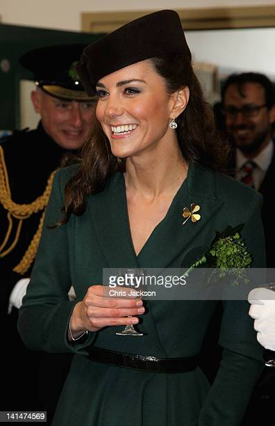 Catherine Duchess of Cambridge holds a glass of Harvey's Bristol Creme in the Junior's Mess as she visits Aldershot Barracks on St Patrick's Day on...