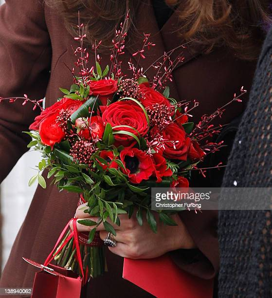 Catherine Duchess of Cambridge holds a posey of red roses and Valentine's Day presents after her visit to charity The Brink an alcoholfree bar which...