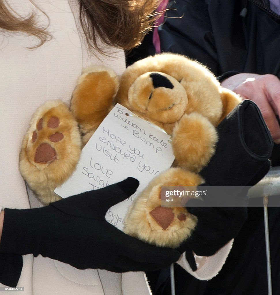 Catherine, Duchess of Cambridge, holds a teddybear she received as a gift during a visit with her husband Prince William, Duke of Cambridge (unseen), to the Child Bereavement, in Saunderton, Buckinghamshire, on March 19, 2013.