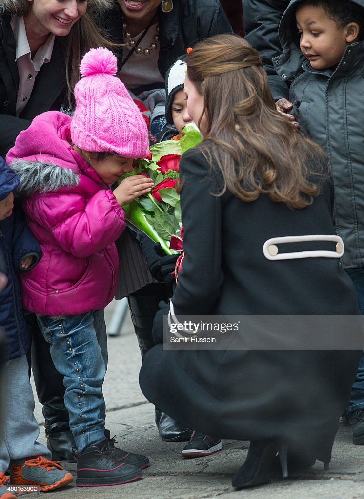 Catherine, Duchess of Cambridge holds flowers for a child to smell as she visits Northside Center for Child Development during her official two-day visit to the United States on December 8, 2014 in New York City.