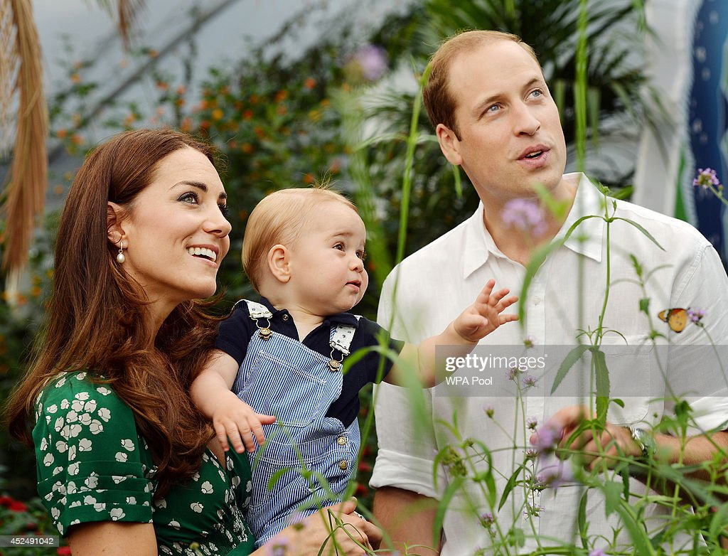Catherine Duchess of Cambridge holds Prince George as he and Prince William Duke of Cambridge's look on while visiting the Sensational Butterflies...