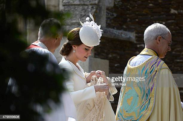 Catherine Duchess of Cambridge holds Princess Charlotte of Cambridge as she arrives with Archbishop of Canterbury Justin Welby at the Church of St...