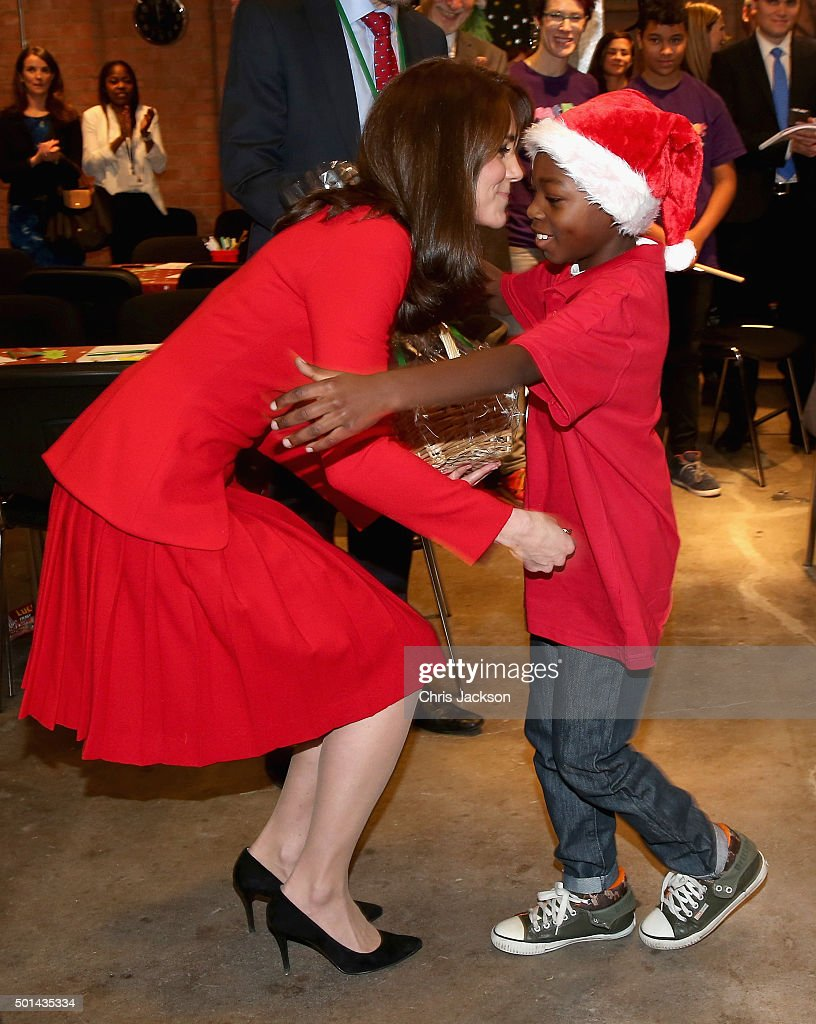 Catherine, Duchess of Cambridge hugs a young boy in a santa hat as she attends the Anna Freud Centre Family School Christmas Party at Anna Freud Centre on December 15, 2015 in London, England. The Duchess joined groups of families in Festive activities designed to help pupils reflect on the positive progress in their social relationships and communication skills.