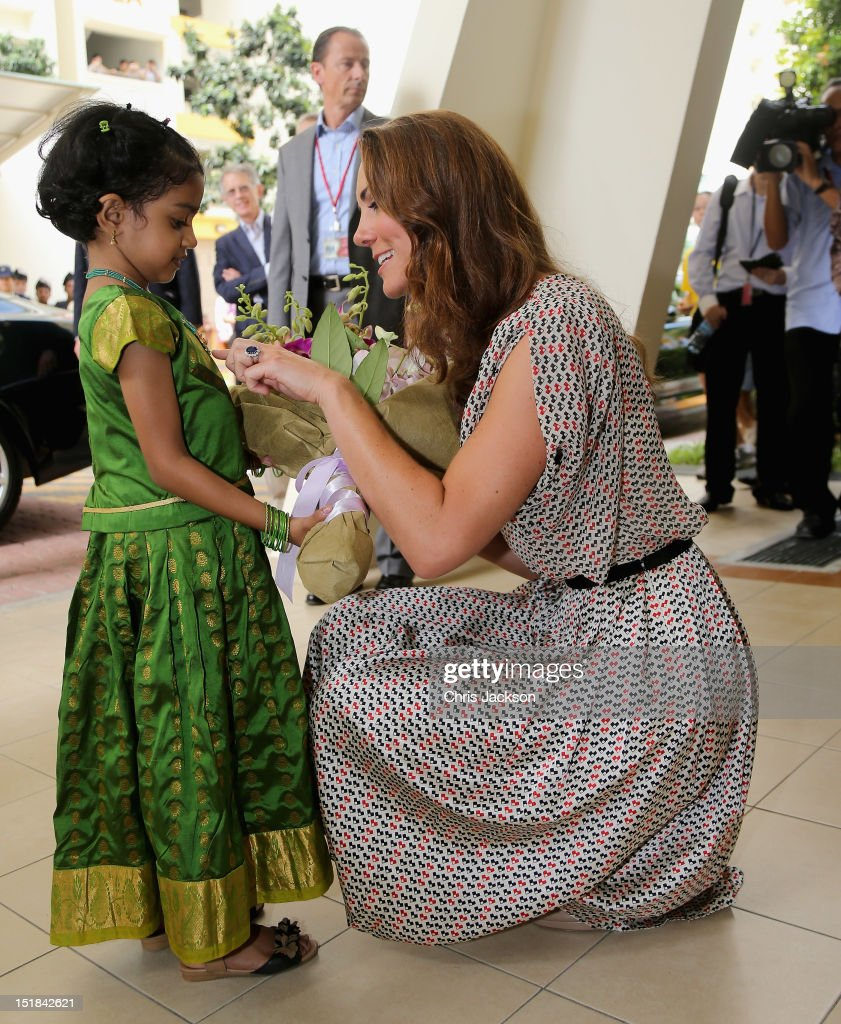 Catherine, Duchess of Cambridge is given flowers by a young girl as she attends a cultural event in Queenstown on day 2 of Prince William, Duke of Cambridge and Catherine, Duchess of Cambridge's Diamond Jubilee Tour of the Far East on September 12, 2012 in Singapore. Prince William, Duke of Cambridge and Catherine, Duchess of Cambridge are on a Diamond Jubilee Tour of the Far East taking in Singapore, Malaysia, the Solomon Islands and the tiny Pacific Island of Tuvalu.