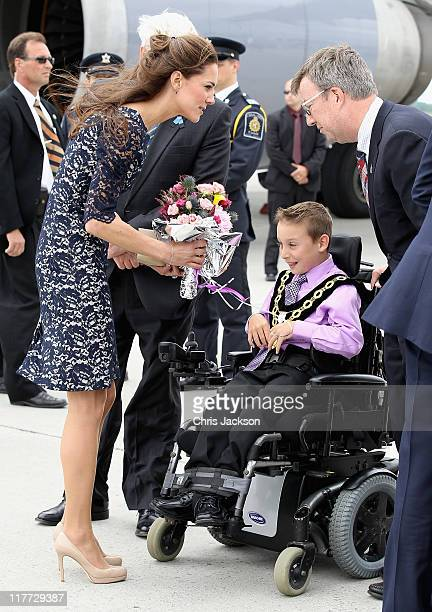 Catherine Duchess of Cambridge is given flowers by Kellen Schleyer as she arrives at MacdonaldCartier International Airport on June 30 2011 in Ottawa...