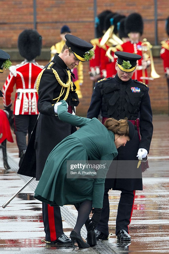 Catherine, Duchess of Cambridge is helped by Prince William, Duke of Cambridge as she gets her heel stuck in the grating while they take part in a St Patrick's Day parade as they visit Aldershot Barracks on St Patrick's Day on March 17, 2013 in Aldershot, England.