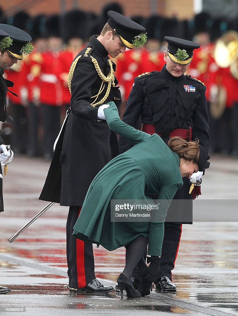 Catherine, Duchess of Cambridge is helped by Prince William, Duke of Cambridge as she gets her heel stuck in a grate during the Irish Guards St Patricks Day Parade on March 17, 2013 in Aldershot, England.