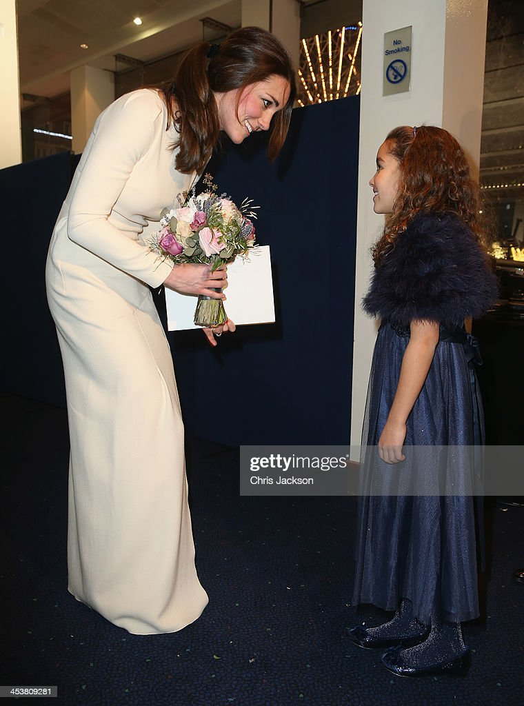 Catherine, Duchess of Cambridge is presented with a bouquet of flowers by a young girl as she attends the Royal film performance of 'Mandela: Long Walk to Freedom' at Odeon Leicester Square on December 5, 2013 in London, England.