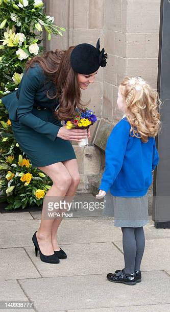 Catherine Duchess of Cambridge is presented with a bouquet of poseys by 7 year old AmyLou Dronfield from Manor C of E School in Leicester city centre...