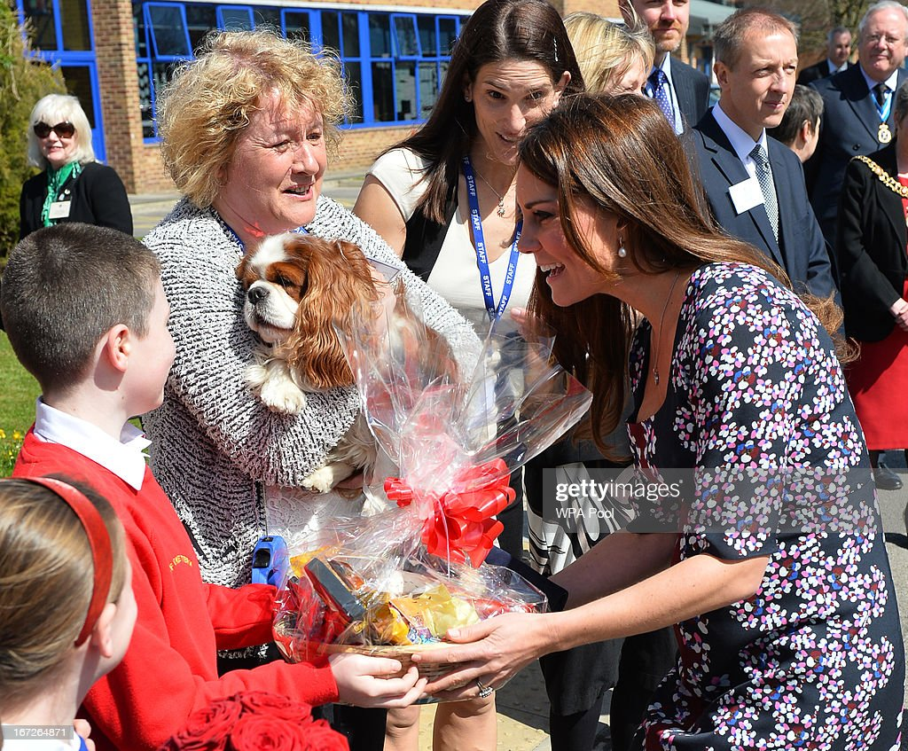 Catherine, Duchess of Cambridge (R), is presented with a gift for her dog Lupo as she meets the school dog Henry as she arrives to visit The Willows Primary School, Wythenshawe to launch a new school counseling program on April 23, 2013 in Manchester, England. The Duchess of Cambridge met staff and volunteers, teachers and parents at the school as she launched the program which is a partnership between the Royal Foundation, Comic Relief, Place2Be and Action on Addiction.