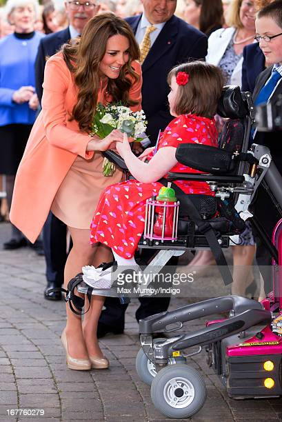 Catherine Duchess of Cambridge is presented with a posy of flowers by Sally Evans as she visits Naomi House Children's Hospice to celebrate...
