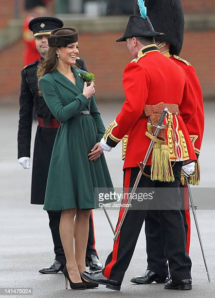 Catherine Duchess of Cambridge is presented with a 'shamrock' as she takes part in a St Patrick's Day parade as she visits Aldershot Barracks on St...