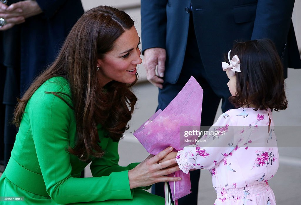 Catherine, Duchess of Cambridge is presented with flowers by a young girl on arrival at the National Portrait Gallery on April 24, 2014 in Canberra, Australia. The Duke and Duchess of Cambridge are on a three-week tour of Australia and New Zealand, the first official trip overseas with their son, Prince George of Cambridge.