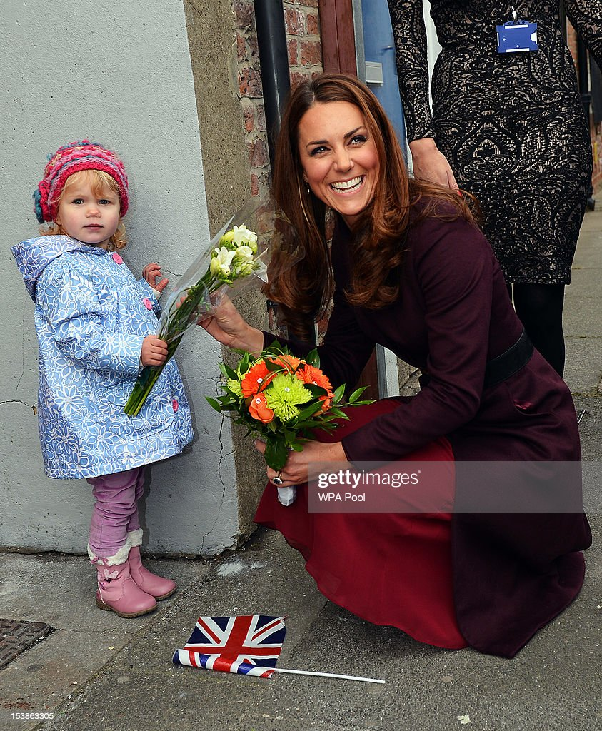 Catherine, Duchess of Cambridge laughs as she receives flowers from two-year-old Lola Mackay - who refused to let go of them - during a visit to the CRI Stockton Recovery Service on October 10, 2012 in Stockton-On-Tees, England.