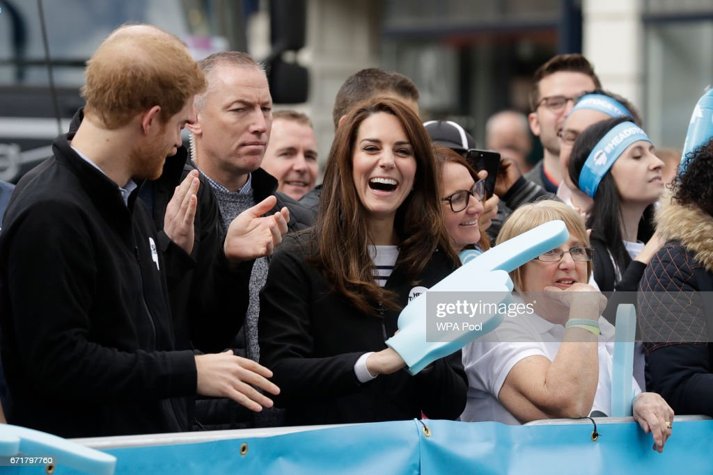 Catherine, Duchess of Cambridge laughs as she wears a big foam hand passed to her to put on by Prince Harry as they cheer on runners at a 'Heads Together' cheering point along the route of The Virgin Money London Marathon 2017 on April 23, 2017 in London, England.