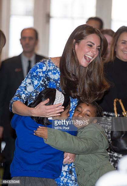 Catherine Duchess of Cambridge laughs with children and representatives from charities and Aardman Animations during a meeting of the Charities Forum...