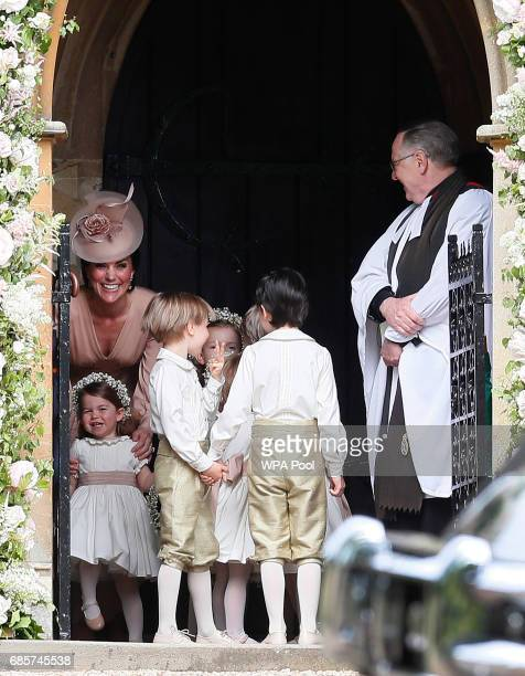 Catherine Duchess of Cambridge left stands with her daughter Princess Charlotte bottom left as they arrive for the wedding of Pippa Middleton and...