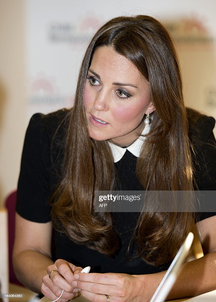 Catherine, Duchess of Cambridge, listens to a boy during a visit with her husband Prince William, Duke of Cambridge (unseen), to the Child Bereavement, in Saunderton, Buckinghamshire, on March 19, 2013.