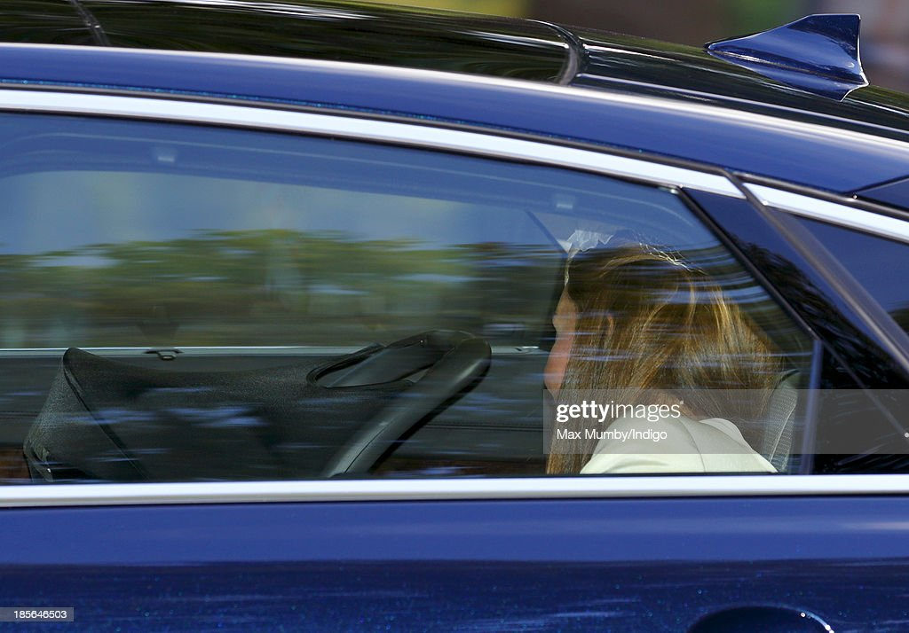 Catherine, Duchess of Cambridge looks at her son Prince George of Cambridge in his car seat as they travel to the Chapel Royal in St James's Palace for Prince George of Cambridge's christening on October 23, 2013 in London, England.