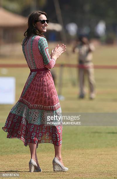 Catherine Duchess of Cambridge looks on as she and Britain's Prince William Duke of Cambridge play a game of cricket with Indian children who are...