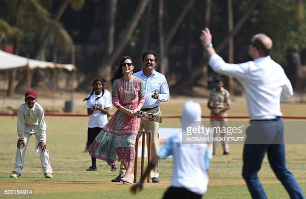 Catherine Duchess of Cambridge looks on as she and Prince William Duke of Cambridge play a game of cricket with Indian children who are beneficiaries...