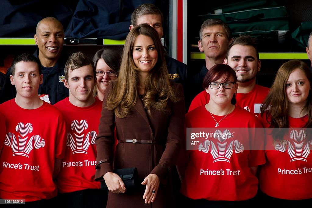 Catherine, Duchess of Cambridge (C) looks towards her staff for guidance after posing for a photograph during her visit to Peaks Lane fire station in Grimsby, north England on March 5, 2013. The Duchess of Cambridge is on an official visit to Grimsby during which she visited the National Fishing Heritage Centre and will meet with unemployed teenagers. AFP PHOTO/Leon Neal