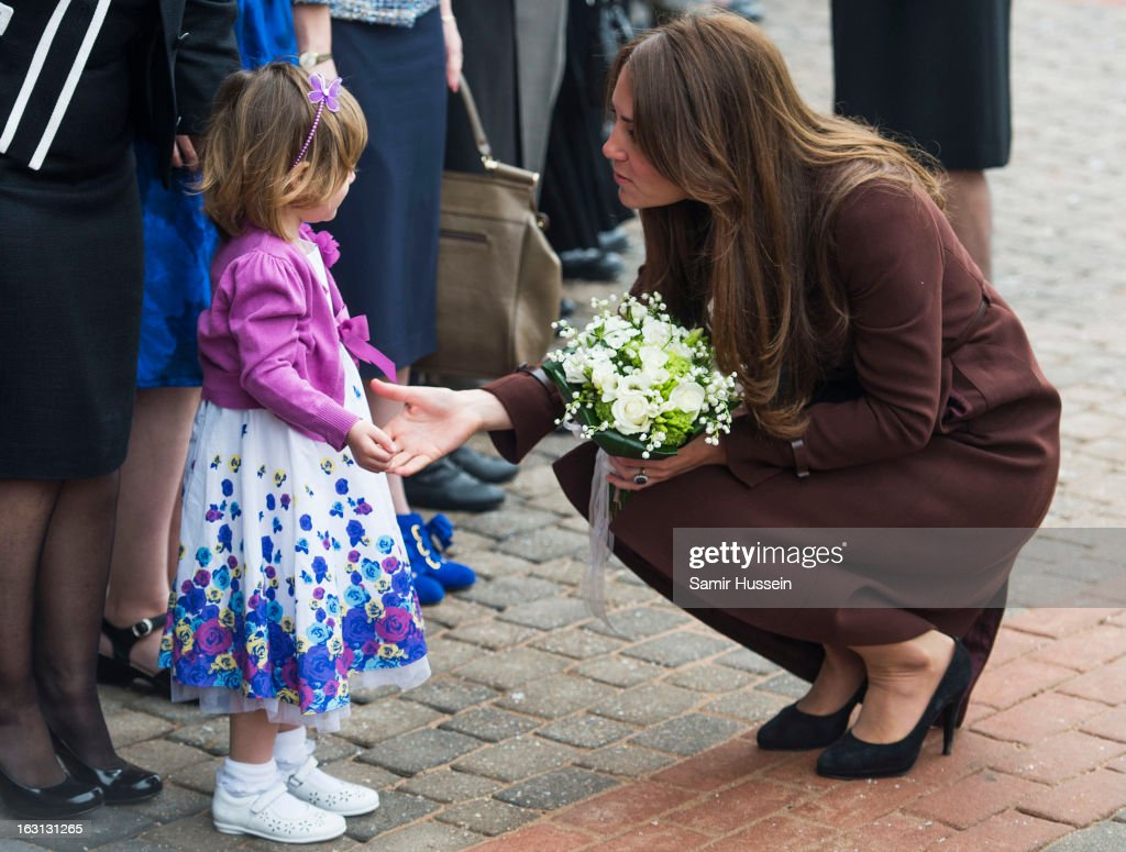 Catherine, Duchess of Cambridge meets a girl as she visits the Fishing Heritage Centre during an official visit to Grimsby on March 5, 2013 in Grimsby, England.