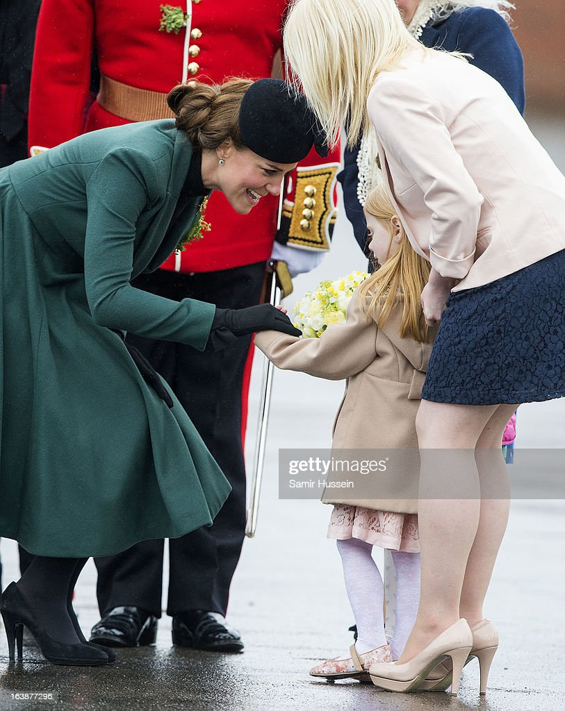 Catherine, Duchess of Cambridge meets a young girl as she attends the Irish Guards' St Patrick's Day Parade at Mons Barracks on March 17, 2013 in Aldershot, England.