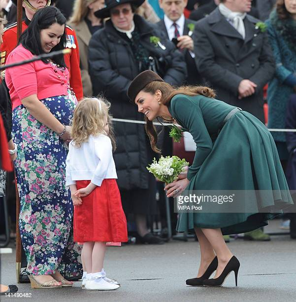 Catherine Duchess of Cambridge meets two young girls who handed her a delicate posy as she presents shamrocks to members of the 1st Battalion Irish...