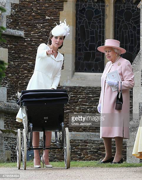 Catherine Duchess of Cambridge points as she pushes Princess Charlotte of Cambridge in her pram as Queen Elizabeth II looks on as they leave the...