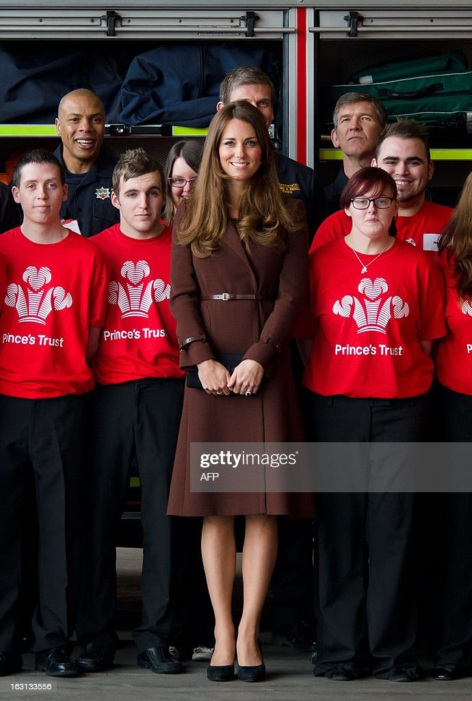 Catherine, Duchess of Cambridge (C) poses for a photograph during her visit to Peaks Lane fire station in Grimsby, northern England on March 5, 2013. The Duchess of Cambridge is on an official visit to Grimsby during which she visited the National Fishing Heritage Centre and will meet with unemployed teenagers. AFP PHOTO/Leon Neal