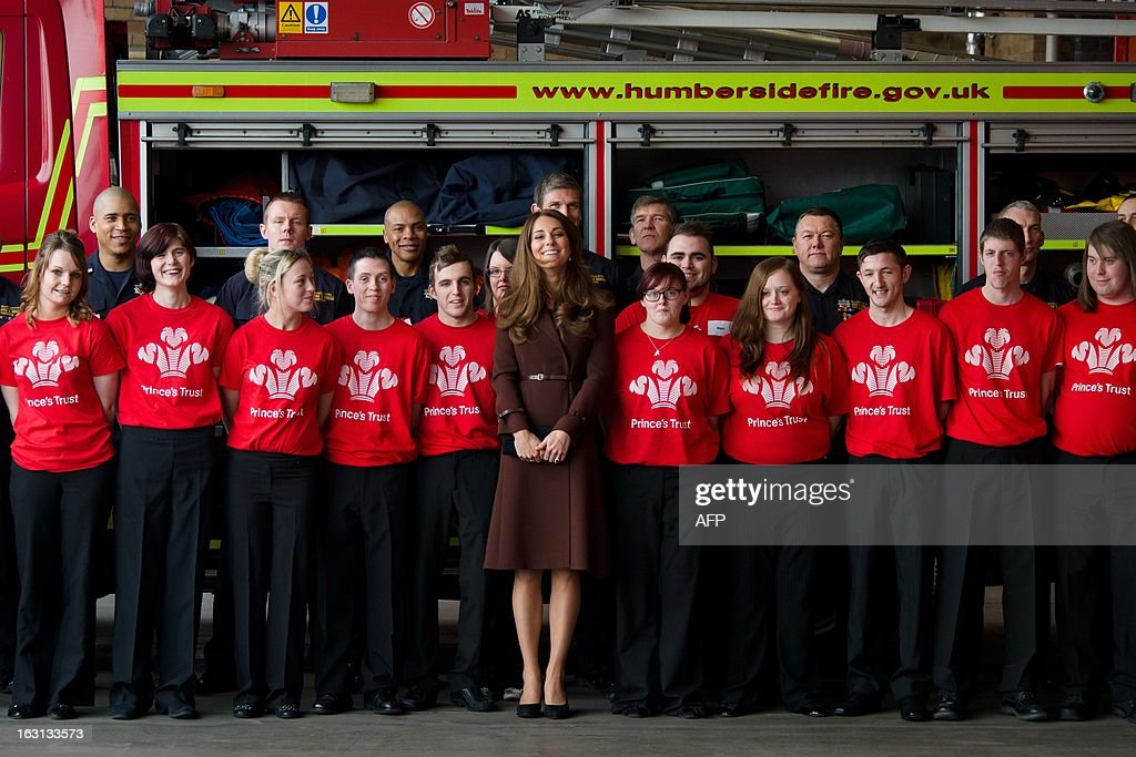 Catherine, Duchess of Cambridge (C) poses for a photograph with firefighters and Princes Trust volunteers during her visit to Peaks Lane fire station in Grimsby, north England on March 5, 2013. The Duchess of Cambridge is on an official visit to Grimsby during which she visited the National Fishing Heritage Centre and will meet with unemployed teenagers. AFP PHOTO/Leon Neal