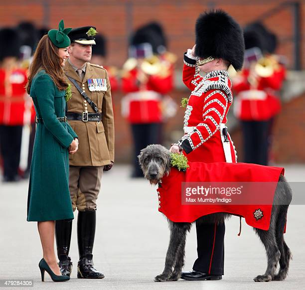 Catherine Duchess of Cambridge presents a Shamrock to Domhnall as she attends the St Patrick's Day Parade at Mons Barracks on March 17 2014 in...