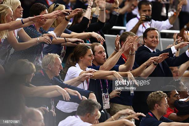 Catherine Duchess of Cambridge Prince William Duke of Cambridge and Prime Minister David Cameron take part in a Mexican wave as they watch the track...