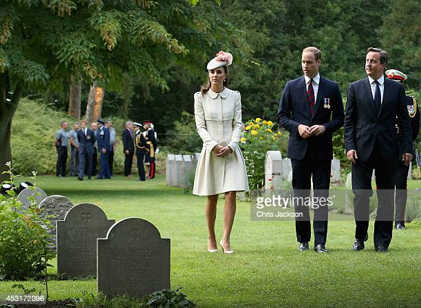 Catherine Duchess of Cambridge Prince William Duke of Cambridge and Prime Minister David Cameron walk through war graves at St Symphorien Military...
