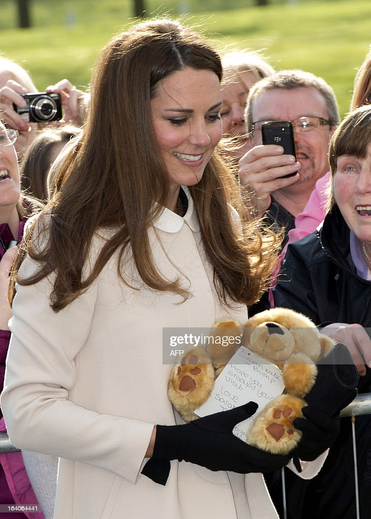 Catherine, Duchess of Cambridge, receive a teddybear during a visit with her husband Prince William, Duke of Cambridge (unseen), to the Child Bereavement, in Saunderton, Buckinghamshire, on March 19, 2013. AFP PHOTO/POOL/PAUL EDWARDS