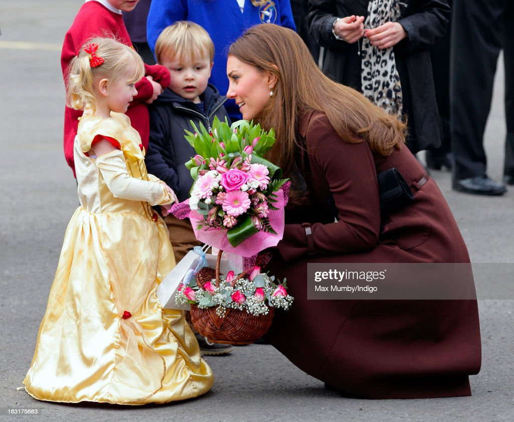Catherine, Duchess of Cambridge receives a posy of flowers from a girl dressed as a princess as she visits Peaks Lane Fire Station whilst carrying out a day of engagements on March 5, 2013 in Grimsby, England.