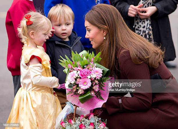 Catherine Duchess of Cambridge receives a posy of flowers from a girl dressed as a princess as she visits Peaks Lane Fire Station whilst carrying out...