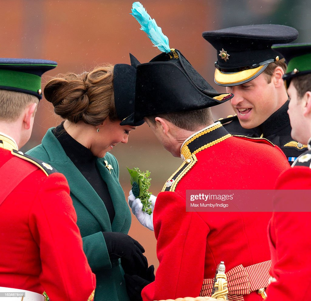 Catherine, Duchess of Cambridge receives a sprig of Shamrock as Prince William, Duke of Cambridge looks on during the St Patrick's Day Parade at Mons Barracks on March 17, 2013 in Aldershot, England.