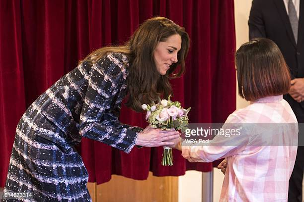 Catherine Duchess of Cambridge recieves a posy of flowers at Francis House which provides end of life care and bereavement support during a visit to...