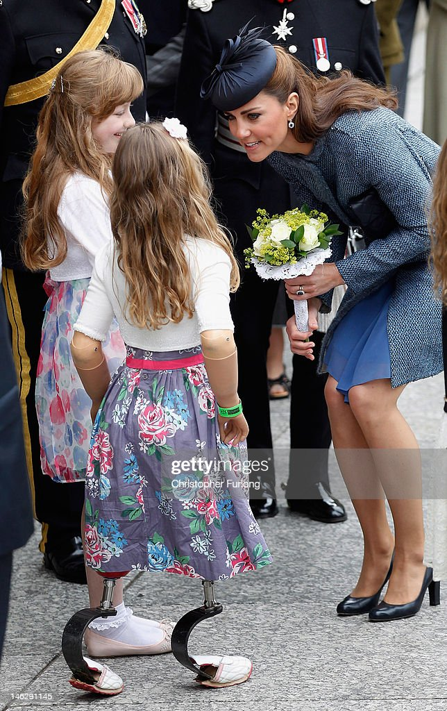Catherine, Duchess of Cambridge smiles as she accepts a posey of flowers from eight-year-old Isabelle Weall (C) outside Nottingham Town Hall during her visit to the East Midlands on June 13, 2012 in Nottingham, England. The Queen was accompanied by Prince William, Duke of Cambridge and Catherine, Duchess of Cambridge, during her official visit to the East Midlands. Prince William will later make his official tribute to the Queen for the Jubilee.