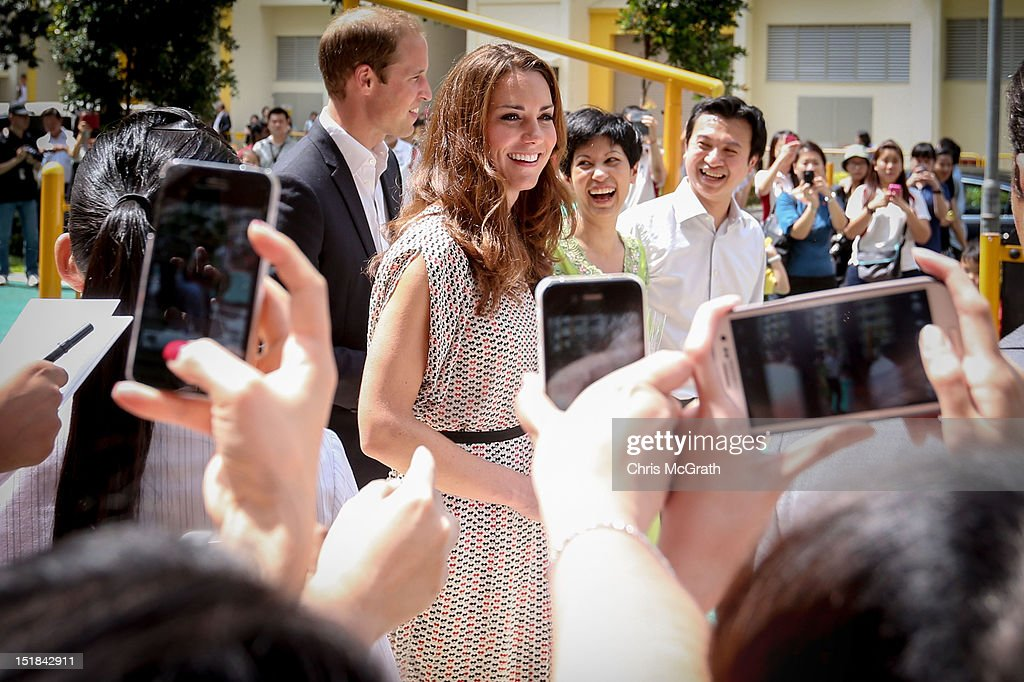 Catherine, Duchess of Cambridge smiles at members of public in the crowd as she walks alongside <a gi-track='captionPersonalityLinkClicked' href=/galleries/search?phrase=Prince+William&family=editorial&specificpeople=178205 ng-click='$event.stopPropagation()'>Prince William</a>, Duke of Cambridge as they visit Strathmore Green housing estate on day 2 of <a gi-track='captionPersonalityLinkClicked' href=/galleries/search?phrase=Prince+William&family=editorial&specificpeople=178205 ng-click='$event.stopPropagation()'>Prince William</a>, Duke of Cambridge and Catherine, Duchess of Cambridge's Diamond Jubilee Tour of the Far East on September 12, 2012 in Singapore. <a gi-track='captionPersonalityLinkClicked' href=/galleries/search?phrase=Prince+William&family=editorial&specificpeople=178205 ng-click='$event.stopPropagation()'>Prince William</a>, Duke of Cambridge and Catherine, Duchess of Cambridge are on a Diamond Jubilee Tour of the Far East taking in Singapore, Malaysia, the Solomon Islands and the tiny Pacific Island of Tuvalu.