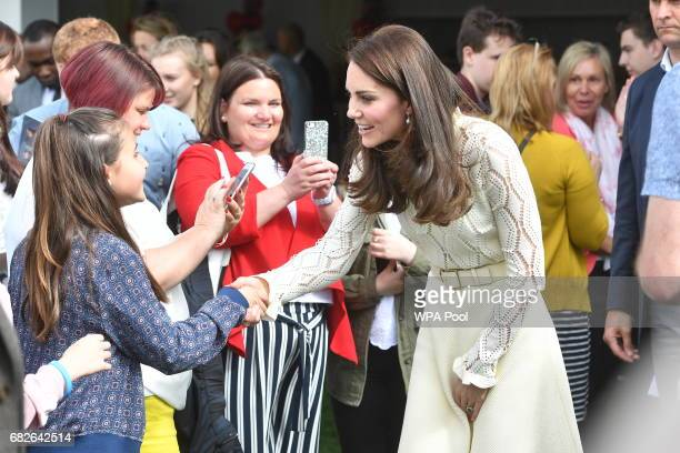 Catherine Duchess of Cambridge speaks to children as she along with Prince William Duke of Cambridge and Prince Harry host Party at The Palace they...