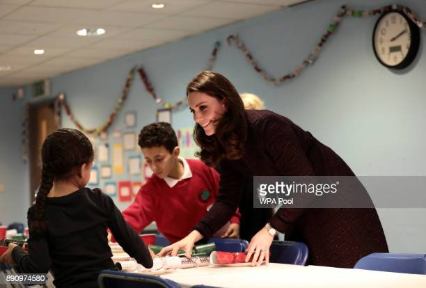 Catherine Duchess of Cambridge speaks to children during a visit to the Rugby Portobello Trust's Christmas party which included children affected by...