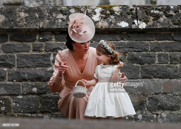 Catherine Duchess of Cambridge speaks to Princess Charlotte after the wedding of Pippa Middleton and James Matthews at St Mark's Church on May 20...