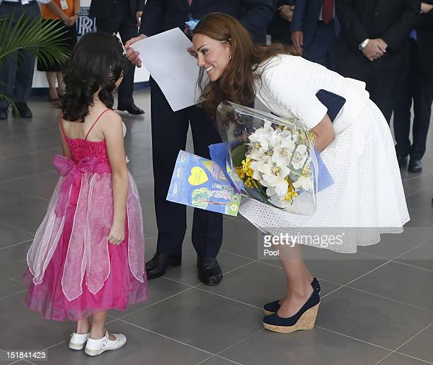 Catherine Duchess of Cambridge speaks with fouryearold Maeve Low as she tours the RollsRoyce Seletar Campus during the Diamond Jubilee tour at...